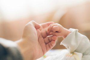 mom holding babies hand
